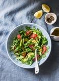 Avocado, grapefruit, rocket salad with mustard olive oil salad dressing on blue background, top view. Vegetarian diet food stock image