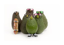 Avocado - Group. A group of California avocados wearing sunglasses, one holding a skateboard, and one wearing black sneakers on white background royalty free stock image