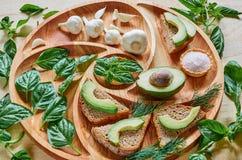 Avocado grzanki na drewnianym talerzu z czosnkiem, basilem, koperem i solą, Weganinu avocado kanapki dekorować z basilów liśćmi Fotografia Stock