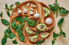 Avocado grzanki na drewnianym talerzu z czosnkiem, basilem, koperem i solą, Weganinu avocado kanapki dekorować z zielonym basilem Zdjęcia Royalty Free