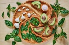 Avocado grzanki na drewnianym talerzu z czosnkiem, basilem, koperem i solą, Weganinu avocado kanapki dekorować z zielonym basilem Zdjęcia Stock