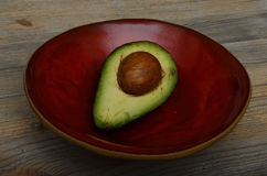 Avocado halb auf einer roten keramischen Schüssel Lizenzfreie Stockfotos