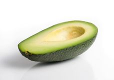 Avocado half. Side view of an avocado half with reflection, isolated on a white background royalty free stock photography