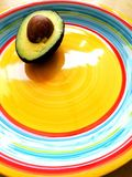 Avocado half. A photograph showing a cut half pear of an avocado with seed intact, placed on a bright colorful plate with Mexican ring colors. Health food stock images