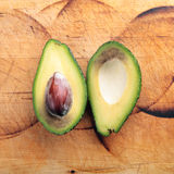 Avocado halves. On wood background royalty free stock photos