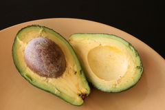 Avocado Halves. Two halves of Avocado on a yellow plate, close up Royalty Free Stock Images
