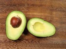 Avocado halves. On a wooden surface Stock Photos