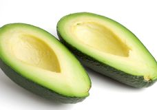 Avocado halves. Side view of two avocado halves, isolated on a white background Royalty Free Stock Image