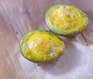 Avocado halves baked with eggs. Close-up on avocado halves baked with eggs inside Stock Photo