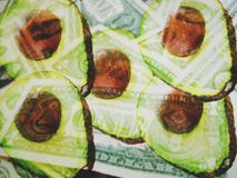 Avocado Halves Blended With Blurred American Dollars. Shallow Depth of Field Double Exposure Background Photography Royalty Free Stock Photos