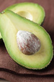 Avocado halves on brown linen napkin Royalty Free Stock Photo