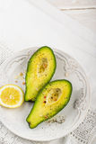 Avocado halves with butter salt and pepper Stock Photo