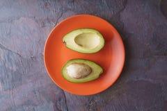 Avocado halves lie on an orange plate on a slate. Horizontal stock photo