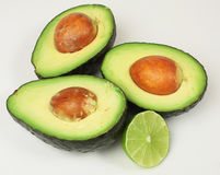 Avocado Halves with Lime Slice. Three avocado halves and lime slice on white background Royalty Free Stock Image