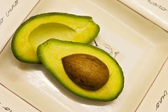 Avocado halves on plate Royalty Free Stock Photos