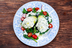 Avocado halves stuffed with cottage cheese and vegetables.  Royalty Free Stock Images