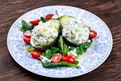 Avocado halves stuffed with cottage cheese and vegetables.  Royalty Free Stock Photo