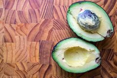 Avocado halves on wodden butchers block board royalty free stock images