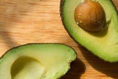 Mexican avocado halves. Avocado halves on wood background Royalty Free Stock Photo