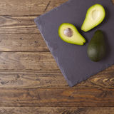 Avocado halves. On a wooden background Royalty Free Stock Photography