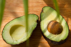 Avocado halves. On wooden background Royalty Free Stock Photos