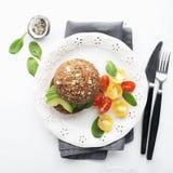 Avocado hamburger z czereśniowymi pomidorami Na lekkim tle Odgórny widok fotografia stock