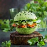 Avocado hamburger z solonym łososiem i świeżymi warzywami Obrazy Royalty Free
