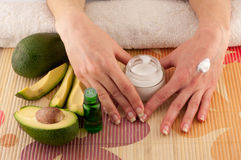 Avocado and Hands. Avocado, butter, cream and female hands on a light background stock photography