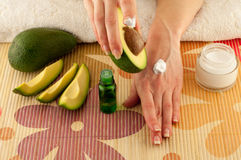 Avocado and Hands. Avocado, butter, cream and female hands on a light background royalty free stock photography