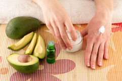 Avocado and Hands. Avocado, butter, cream and female hands on a light background stock photo