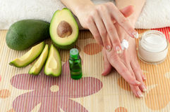 Avocado and Hands. Avocado, butter, cream and female hands on a light background stock images