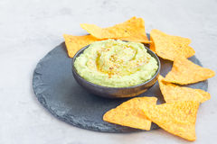 Avocado hummus sprinkled with olive oil, paprika and sesame, served with nachos, horizontal Royalty Free Stock Photo