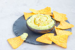 Avocado hummus sprinkled with olive oil, paprika and sesame, served with nachos, horizontal Royalty Free Stock Photos