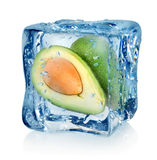 Avocado in ice cube. On a white background Stock Photos