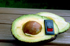 Avocado with inserted power switch. Royalty Free Stock Images