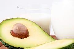 Avocado isolato su un fondo bianco Con il piatto di legno e del bicchiere di latte Alimento sano immagine stock libera da diritti