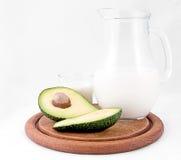 Avocado isolato su un fondo bianco Con il piatto di legno e del bicchiere di latte Alimento sano immagini stock libere da diritti