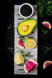 Avocado, kalk en watermeloenradijs op een donkere achtergrond Stock Afbeeldingen