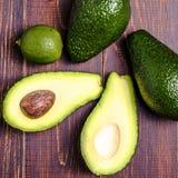 Avocado, kalk op een bruine achtergrond Stock Fotografie