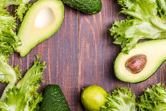 Avocado, kalk, salade op een bruine achtergrond Royalty-vrije Stock Foto's