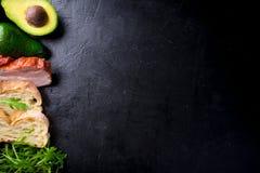 Avocado kanapka na domowej roboty ciabatta chlebie robić z świeżymi pokrojonymi avocados i smażącym crispy bekonem od above Odgór Fotografia Stock