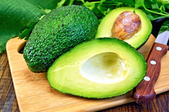 Avocado with knife on board royalty free stock photography