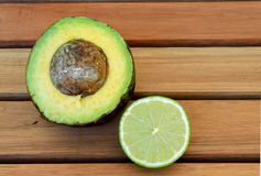 Avocado and Lemon on the table. Half of an avocado and half of a lemon on a wood table Royalty Free Stock Photos