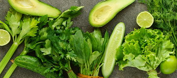 Avocado, lime, cucumber, celery, lettuce and fresh herbs. On a gray stone background Stock Photo