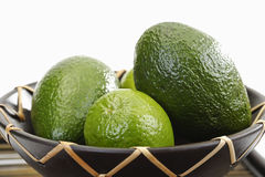 Avocado and lime fruit in bowl Stock Photos