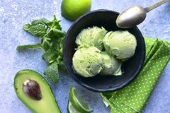 Avocado lime mint ice cream.Top view . Avocado lime mint ice cream in a black bowl over light grey slate, stone or concrete background.Top view royalty free stock images