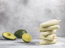 Avocado lime popsicle, copy space. Homemade raw vegan avocado lime popsicle. Sugar-free, non-dairy green ice cream on gray cement textured background. Copy space stock images