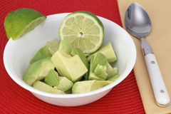 Avocado with Lime Wedges Stock Images