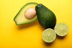 Avocado and lime on yellow background Royalty Free Stock Photo