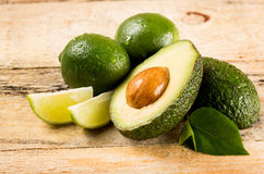 Avocado and limes on wooden background Stock Photos